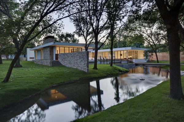 Privacy was important to the family, but they also wanted large expanses of glass through which to enjoy the trees and pond. The solution was a clever C-shaped courtyard plan that shields the home's open interior. Photo 7 of Preston Hollow modern home