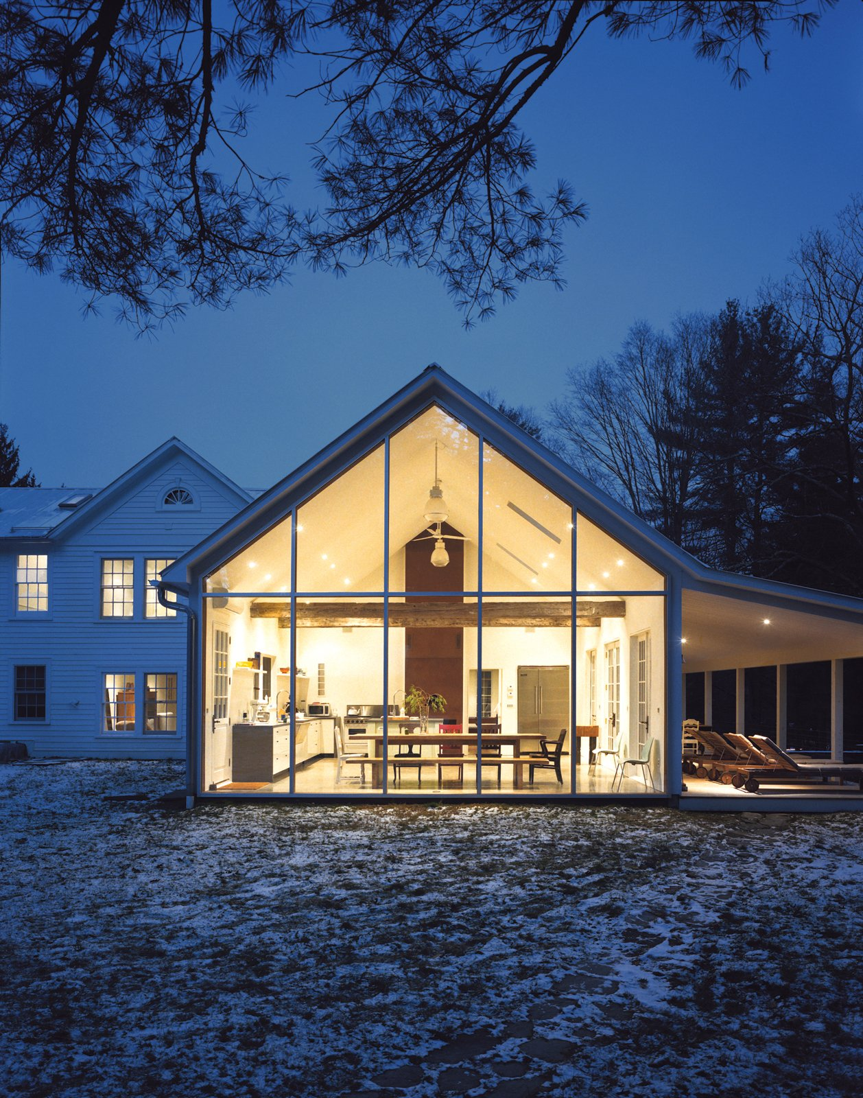 The Floating Farmhouse's semitransparent addition has a roofline that matches the pitch of the original 1820s farmhouse. A porch, tucked under the side eaves, is cantilevered over a stream that runs through the property. Ikea loungers are illuminated from the interior by commercial gymnasium lights repurposed as pendant lamps. Hope Floats - Photo 8 of 12