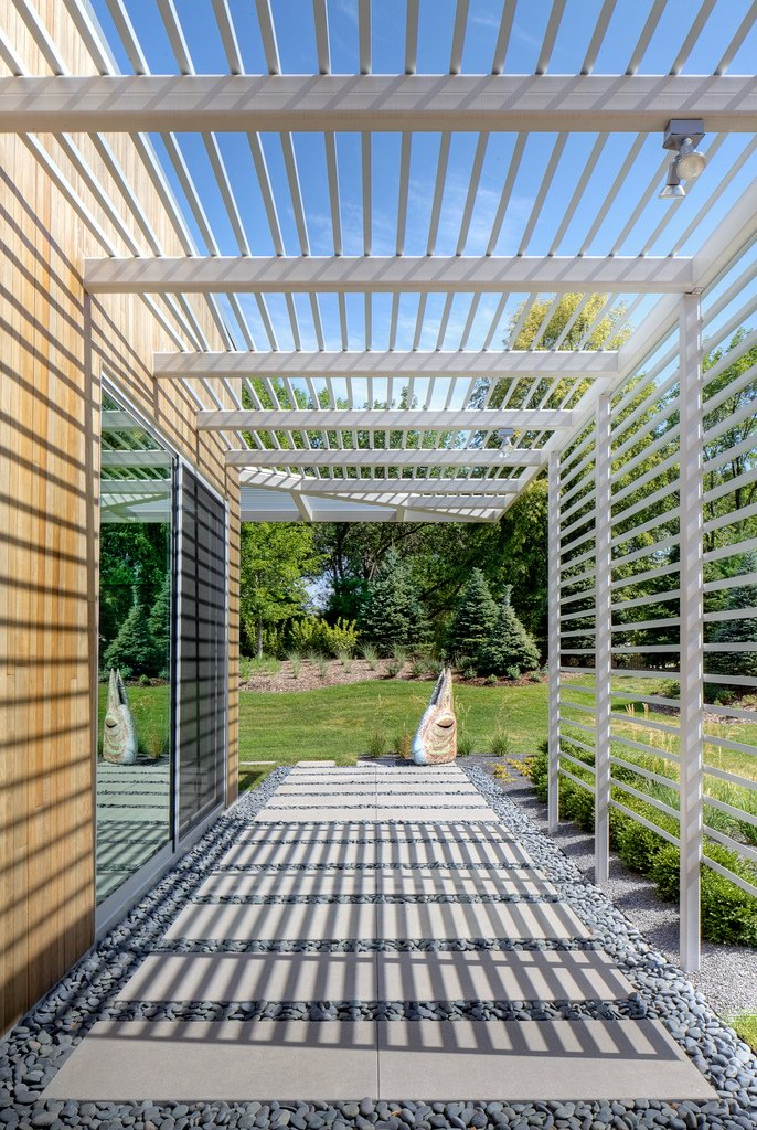 Tack Architects designed the house to frame views of the surrounding landscape. The trellis offers shading and controls the amount of daylight that shines inside (and creates a dramatic passage along the house's perimeter). Omaha Art-Inspired House by Diana Budds