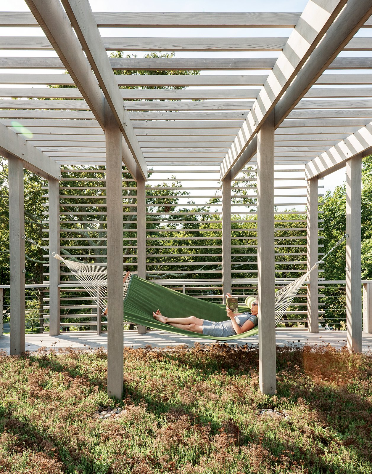 A second green roof is planted with sedum and plays host to one of the family's favorite spots: a hammock. Bentheim suggested adding a trellis overhead to soften and balance the appearance of the facade. Tagged: Outdoor and Back Yard.  Photo 9 of 11 in An Unconventional Prefab on Fishers Island
