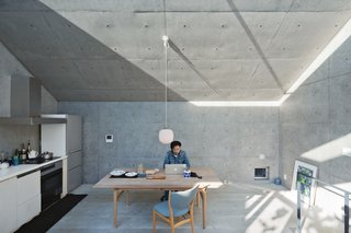 Open-Plan Concrete Home in Japan - Photo 7 of 7 - Nakada works from an Alvar Aalto table in the living and dining area, adjacent to the kitchen. He saved on some elements, such as the plywood cabinetry, and splurged on others, such as the Finn Juhl chairs and Vilhelm Lauritzen lamp. A skylight beneath the angled roof allows in a sliver of constantly changing light.