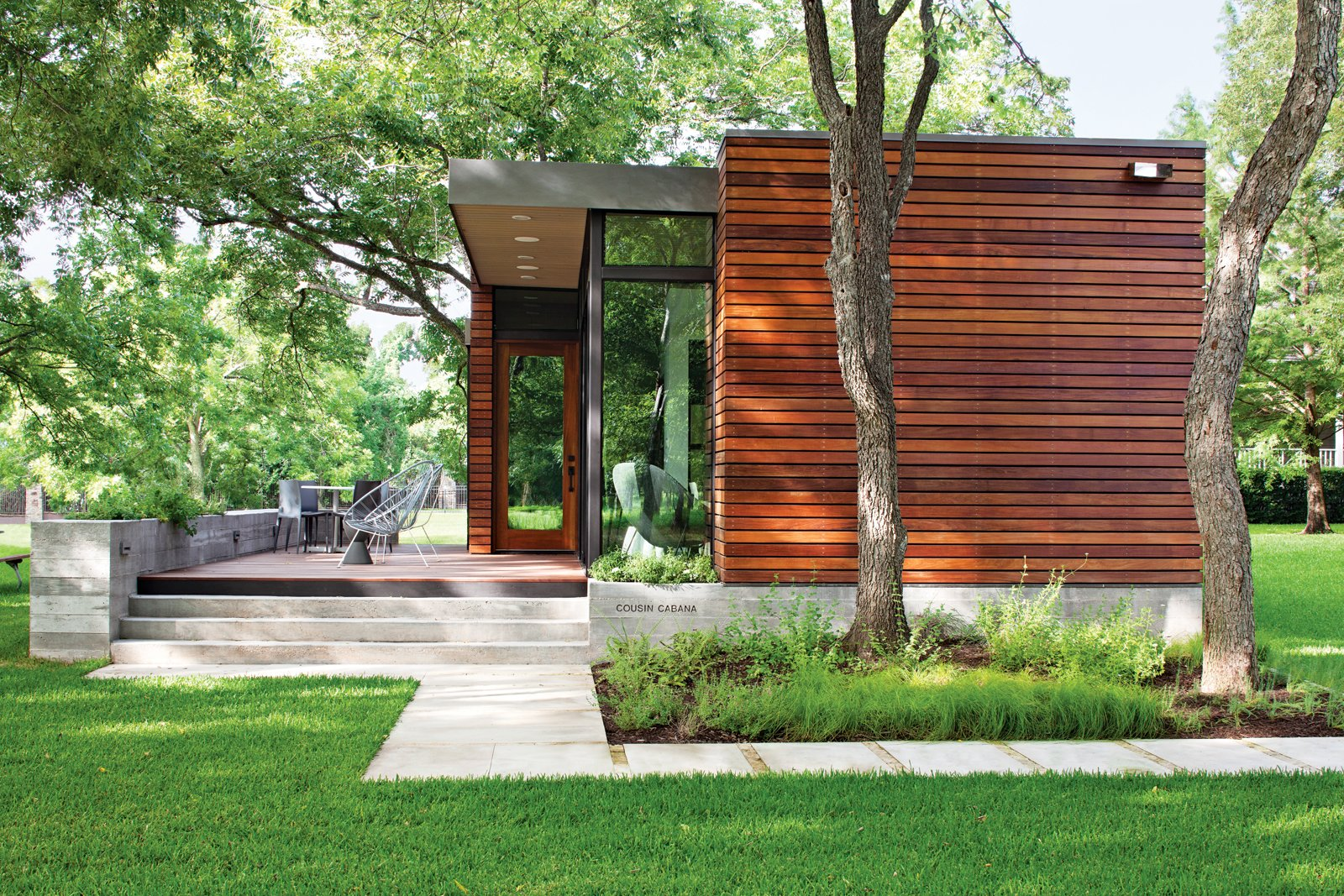 Landscape architect Tait Moring installed pavers around the structure's perimeter and kept the tree cover intact. Photo by: Kimberly Davis  Tiny Homes  by Erika Heet from Small and Modern: A Family Lakeside Getaway in Texas
