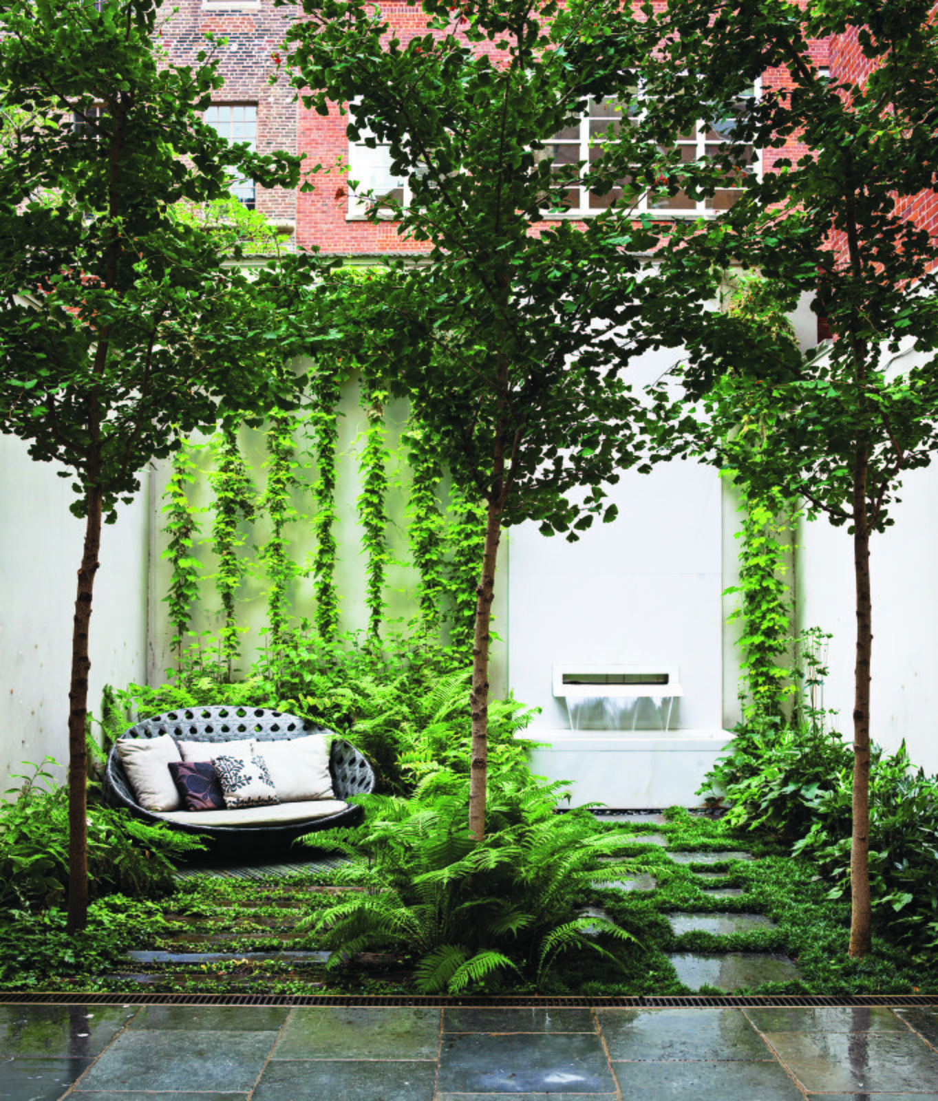 B&B Italia Outdoor's Canasta sofa, by Patricia Urquiola, shares a shady patch in the ground-floor Carnegie Hill garden with three ginkgo biloba trees, an existing fountain with an Italian marble spout designed by Thomas Woltz, and bluestone pavers. The terrace is filled with woodland greenery: Leucothoe, ostrich ferns, and lady ferns.  Small footprint by Rex Ritter from Nelson Byrd Woltz Harnesses the Natural Elements