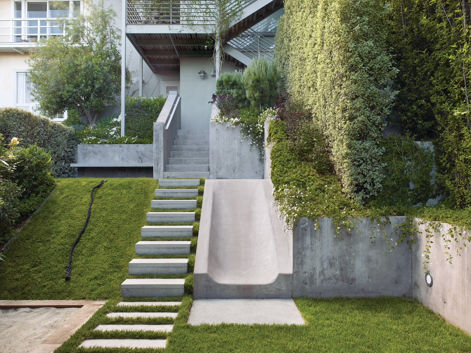 Rather than resist the natural slope of the Buena Vista Heights backyard, landscape architect Eric Blasen composed a well-considered, minimal, multiterraced space. Accent details, like the flat handrail and stone stairs, mirror those repeated both inside the home and out front, respectively; Blasen worked directly with architect Tim Gemmill to ensure a cohesive feel between the spaces. Photo by Marion Brenner. Tagged: Outdoor.  Photo 4 of 4 in Good Clean Fun