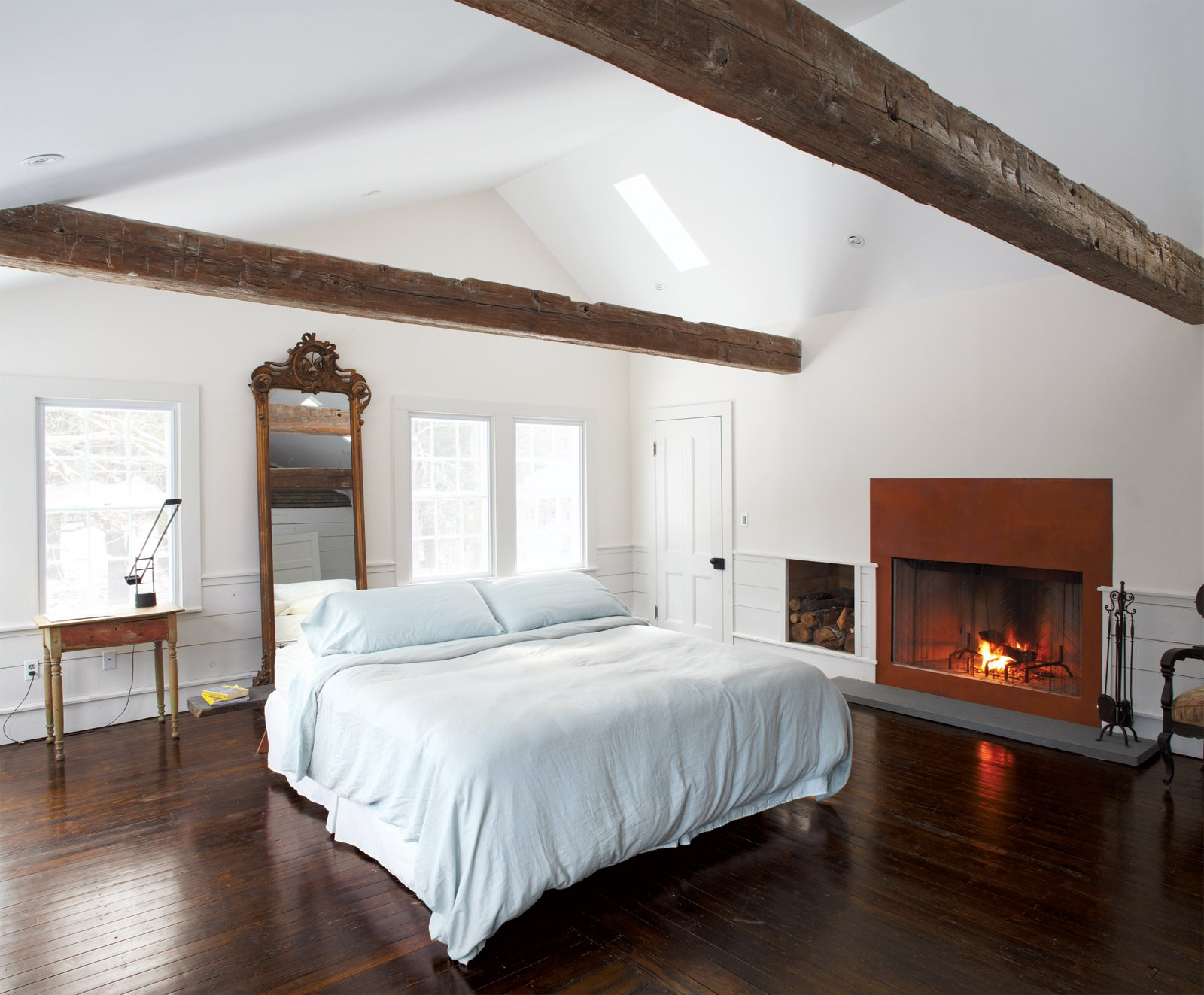 A gas fireplace fronted in weathered steel warms   up the lofty master bedroom, whose spare decor is framed with beams discovered in a Pennsylvania barn. The Tizio desk lamp is by Artemide.  Photo 9 of 12 in Hope Floats