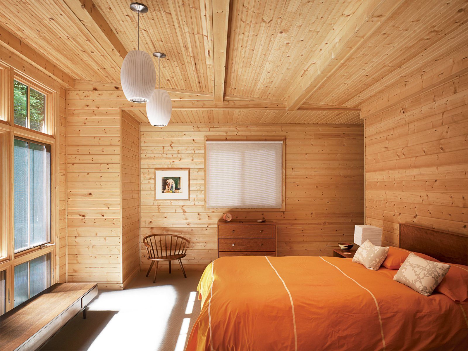 A tastefully spare selection of vintage pieces accents the warm knotty pine in the master bedroom of the Campbell home. The orientation of the room maximizes the picture window that replaced the original garage door. Campbell designed a closet in an alcove behind the wall at the head of the bed.  Bedrooms by Dwell from Comfy Cozy Bedrooms