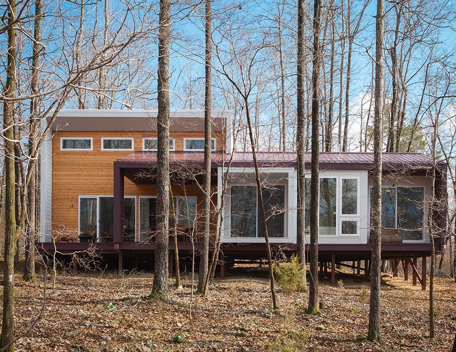 "Cement panels painted a plum hue clad Jason Gordon's 1,157-square-foot cabin in the Ozark Mountains. Architect German Brun and partner Lizmarie Esparza originally specified wood, but opted for the much less expensive material from James Hardie after contractor Damian Fitzpatrick recommended it. ""It was an exercise in cost engineering,"" Brun says.  Photo 33 of 101 in 101 Best Modern Cabins from How to Build an Off-the-Grid Cabin in Arkansas for just over $118,000"
