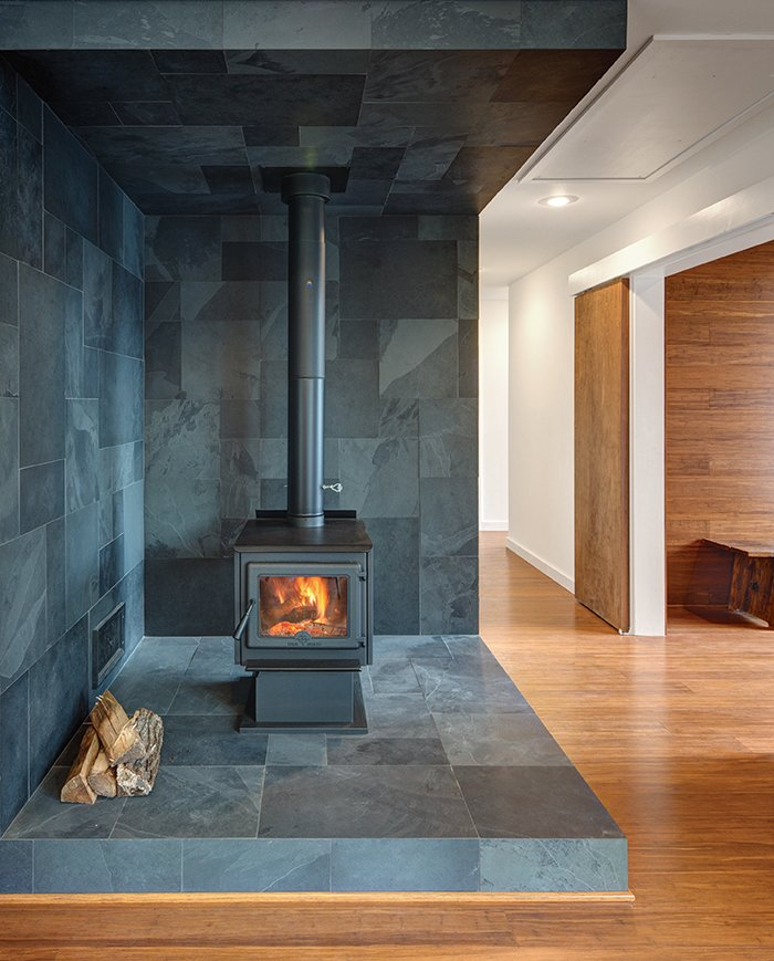 Vermont slate covers the area around the True North wood stove.  Wide-plank Yanachi Carbonized Strand Woven Bamboo covers the floors.
