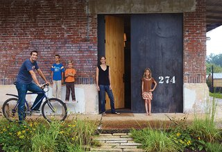 Architect David Hill, his wife, Elizabeth, and their three children (from left: Wade, eight, Luke, six, and Breyton, ten), have an unusual home by the standards of their college-town setting in Auburn, Alabama. Built in 1920, the industrial brick building has had previous incarnations as a church, a recycling center, and a pool hall, among others.