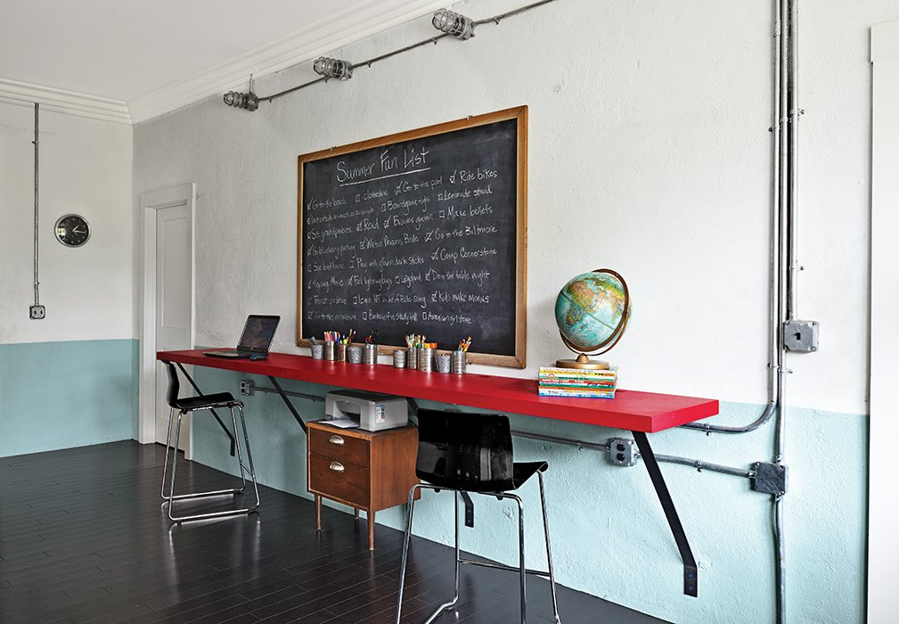 "The tables in the kids' study hall are ""plywood specials,"" David's term for the furniture he built himself.  ""There is something so good about living in the South: the culture, the innovation, the values, the thrift,"" he says.  Photo 2 of 13 in Family-Friendly Renovation of a Brick Warehouse in Alabama"
