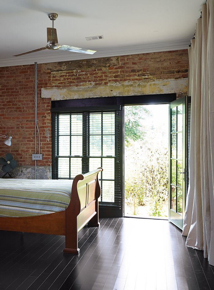 Throughout the house, as in the master bedroom, industrial ceiling fans from Westinghouse, combined with the thick brick walls, keep the need for air conditioning to a minimum. The bed is from Bob Timberlake.  Photo 5 of 13 in Family-Friendly Renovation of a Brick Warehouse in Alabama