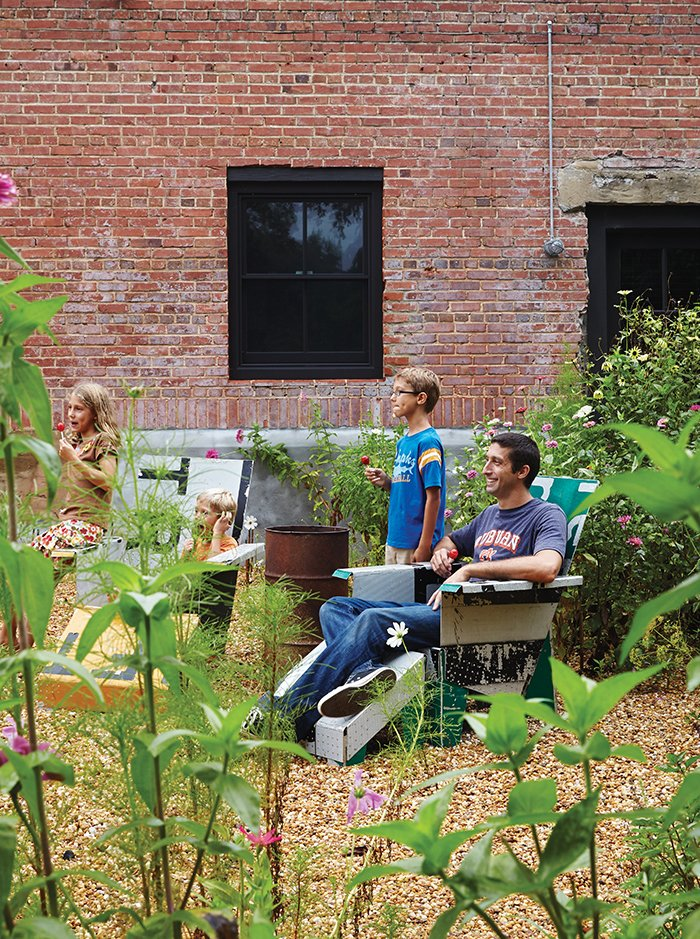 David and Elizabeth built the lawn chairs in the garden from old signs.  Photo 7 of 13 in Family-Friendly Renovation of a Brick Warehouse in Alabama