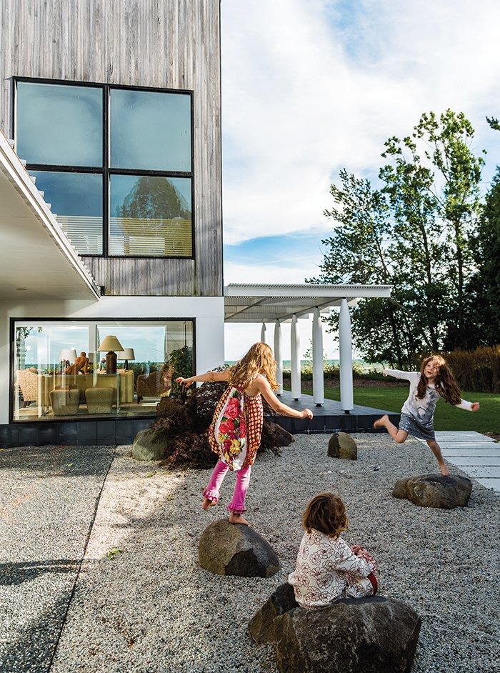 "Julie Brogan's three grandchildren—frequent visitors to her lakeside house in Sturgeon Bay, Wisconsin—can often be found playing on the crushed slate in the courtyard or romping in a corridor that has come to be known as the ""galloping hall.""  Photo 1 of 8 in A Modern Lakeside Home in Wisconsin"