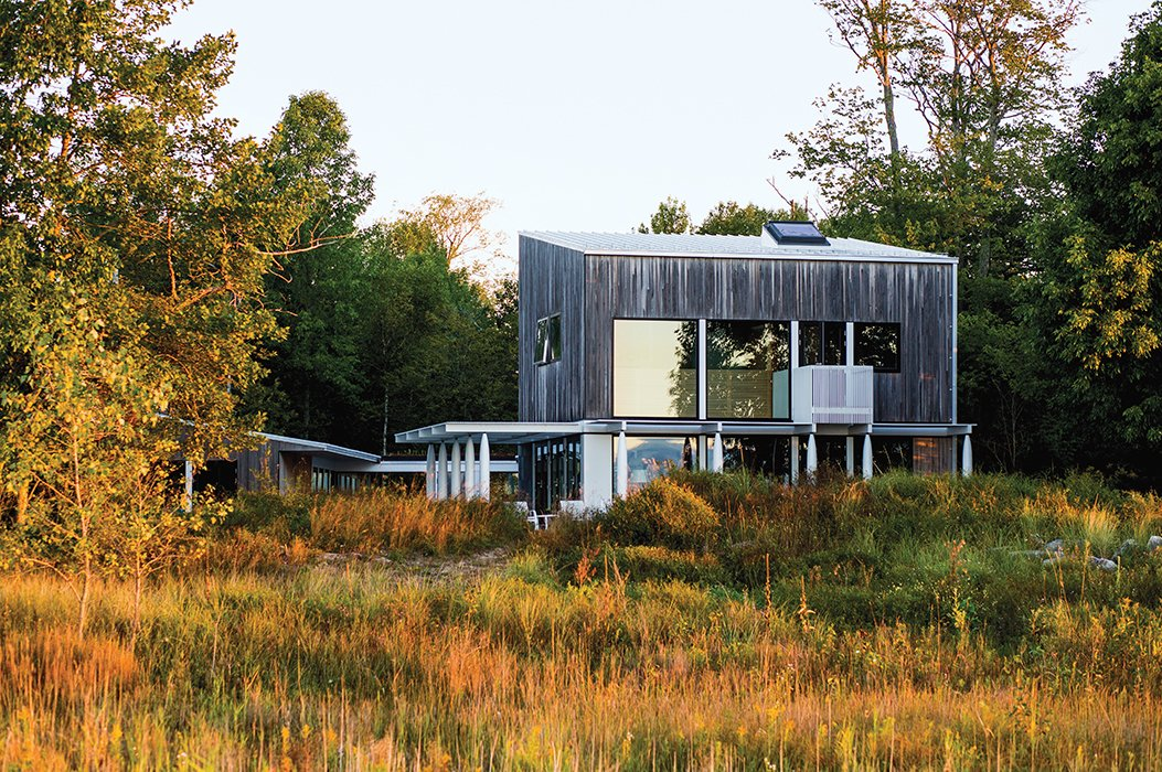 Brogan's home overlooking Lake Michigan is clad in tongue-and-groove new-growth cypress. Vertical basswood slats follow the stairs to the second floor and into the master bedroom, extending outside to serve as the railing for a small balcony.  Photo 3 of 8 in A Modern Lakeside Home in Wisconsin