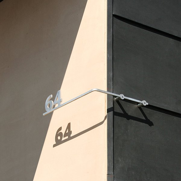 The play of shadows on the iconic shape, as well as on the shapes of the house numbers, is a Levy trademark.