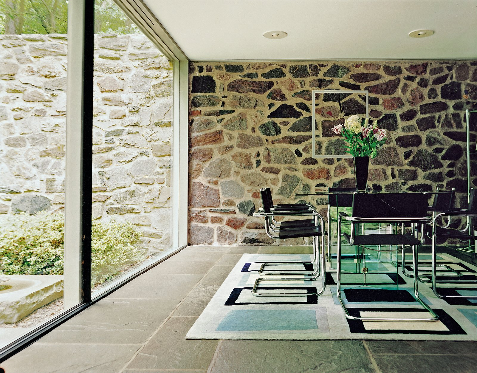 Three stark planes make the dining room a place of sun and shadow: a wall of rock, a floor of bluestone, and a sheer slice of glass. Further adding to the unity of the house, the tubular steel dining chairs were also designed by Breuer. Tagged: Dining Room, Chair, Table, Rug Floor, and Slate Floor.  marcel breuer from Marcel Breuer Hooper House II