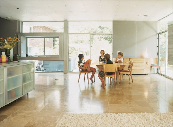 The kids gather around the Heywood-Wakefield dining set, which Terry purchased from Mainly Art in Cincinnati. The flooring in the kitchen and living area is honed travertine from The Great Indoors.