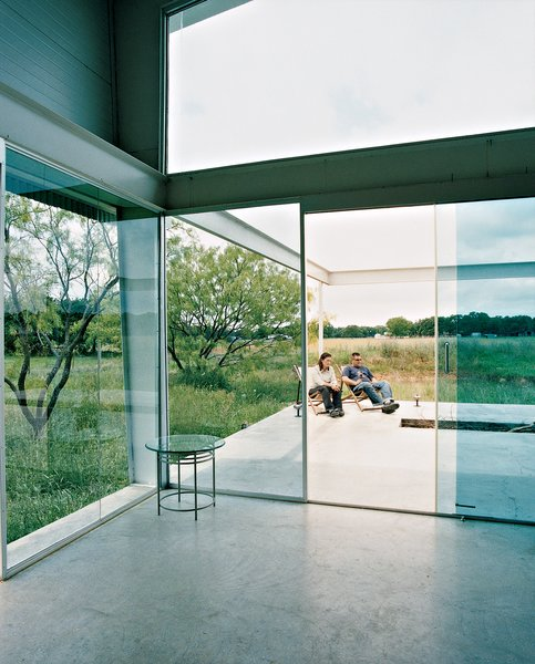 A continuous concrete slab runs from inside the house out to the open deck, which is exposed to the wind that sweeps the surrounding fields.