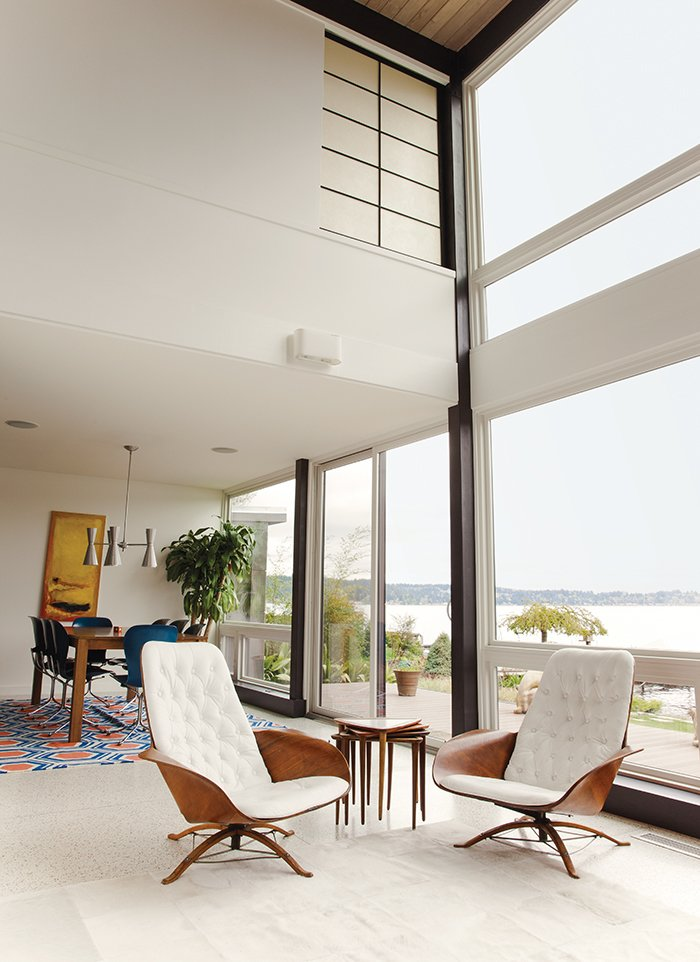 Central to the living room is a pair of George Mulhauser for Plycraft chairs. The adjacent dining room sports a Galaxy chandelier from Rejuvenation, a custom table, and Gideon Kramer Ion chairs. Midcentury Homes by Dwell