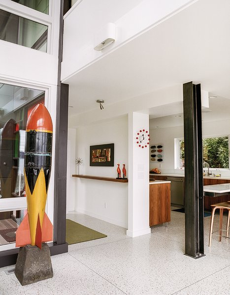 """The entrance opens to the living area, in which an I-beam stands where the kitchen enclosure was. """"It was really tight, so we wanted to push back the wall that was in front of the door,"""" Julien says. The couple traded the old carpet for terrazzo flooring. Julien found the test bomb at an antiques mall."""