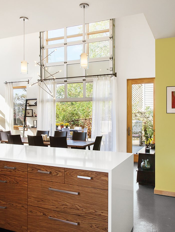A Batons chandelier from LBL Lighting hangs over the dining table. A garage-style door by Overhead Door opens onto a patio that gets plenty of use when the weather cooperates.