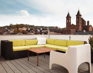 "The roof deck, with views of the nearby St. Augustine church and beyond to downtown Pittsburgh, features partially recycled plastic decking from Rhino Deck and a custom galvanized-steel railing with frosted Plexiglas panels. ""Pittsburgh's one of those cities that if you grew up here, it has a draw that pulls you back,"" Moss says."
