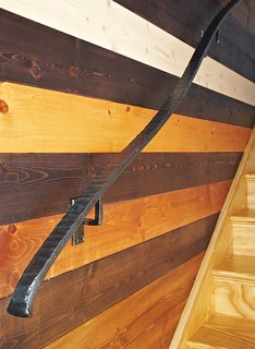 "One of the couple's favorite elements is the tongue-and-groove wall by the stairs. After staining and finishing the Douglas fir boards themselves, they gave their contractor a mathematical pattern developed by their teenage son, Griffin. ""It's like a puzzle for people to try and figure out,"" Moss says. Carrier designed the curvilinear steel railing."