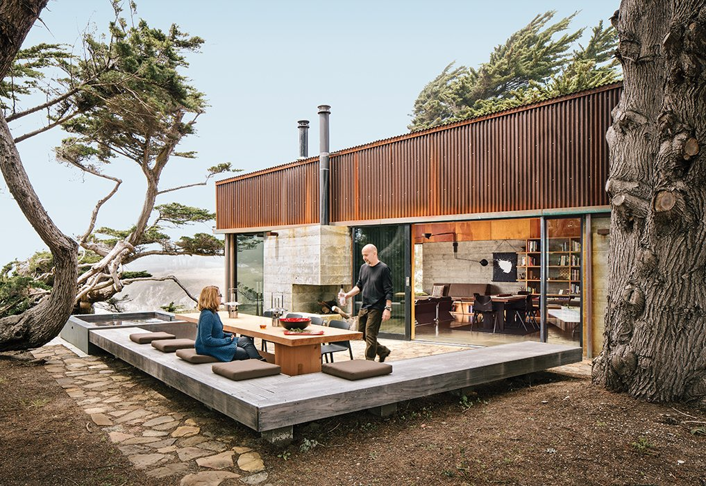 Ramirez and his partner, Sarah Mason Williams, dine at a sequoia table by Redwood Burl next to a hulking juniper tree that they asked the architects to preserve as a centerpiece of the property. Tagged: Exterior, House, Flat RoofLine, Metal Siding Material, and Concrete Siding Material.  Best Photos from Modern Home Joins a Storied Site on the Pacific Ocean