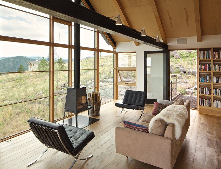 In the living area are a pair of original Barcelona chairs, handed down by del Gaudio's parents. The Shaker stove is by Wittus. Fifty-one crates were used to make the bookshelves, which were fabricated assembly-line-style by the framers from Morningstar Homes.  Photo 7 of 7 in Sustainable Retreat on a Fire-Devastated Site in Boulder