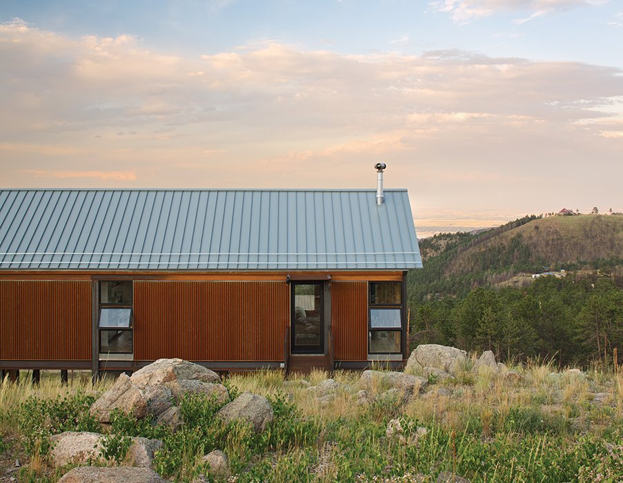 The fire-resistant structure is clad in corrugated Cor-Ten steel that has been left to rust for easy maintenance. Instead of fussy landscaping, the family spread seed for native grasses and wildflowers that they let fill in naturally.  Photo 4 of 7 in Sustainable Retreat on a Fire-Devastated Site in Boulder