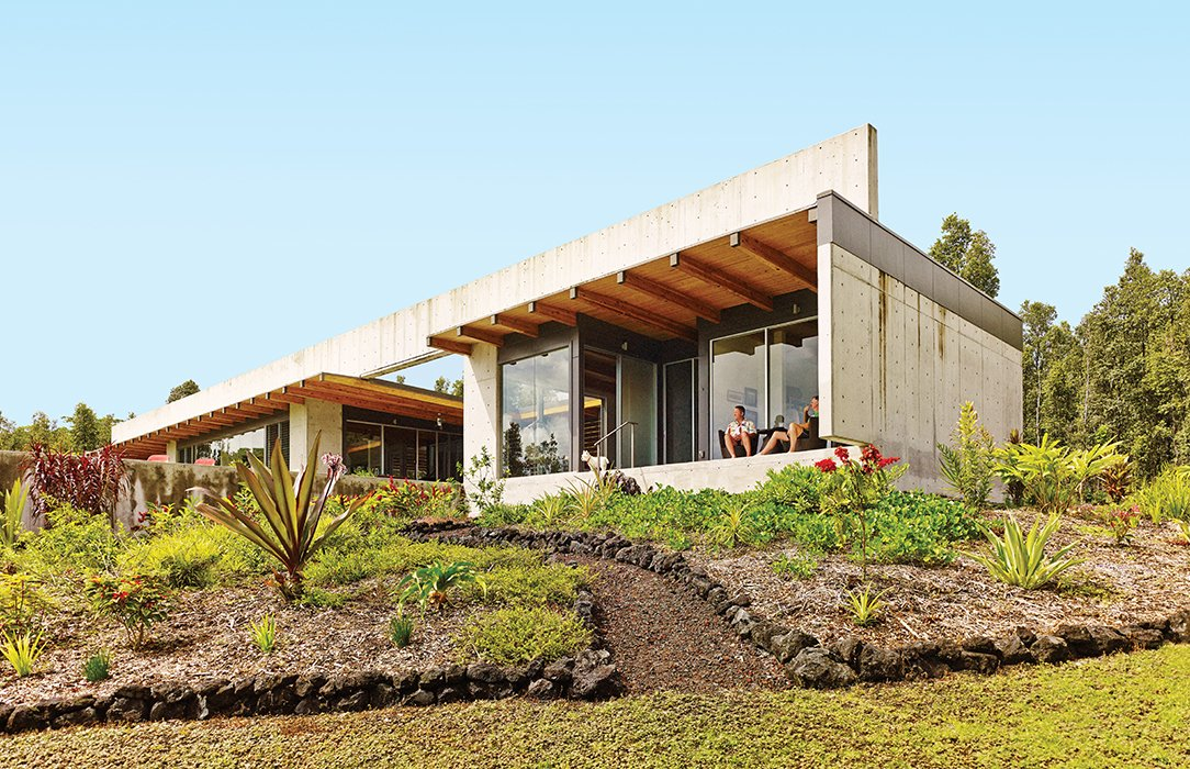 The defining gesture of a house on the Big Island of Hawaii by architect Craig Steely is a 139-foot-long, four-foot-tall concrete beam spanning the roof. Owners Craig Mayer and Rick Penland relax on the lanai, or porch. Tagged: Back Yard, Exterior, Concrete Siding Material, House, and Flat RoofLine.  Photo 1 of 7 in This House Conquers the Big Island in Hawaii