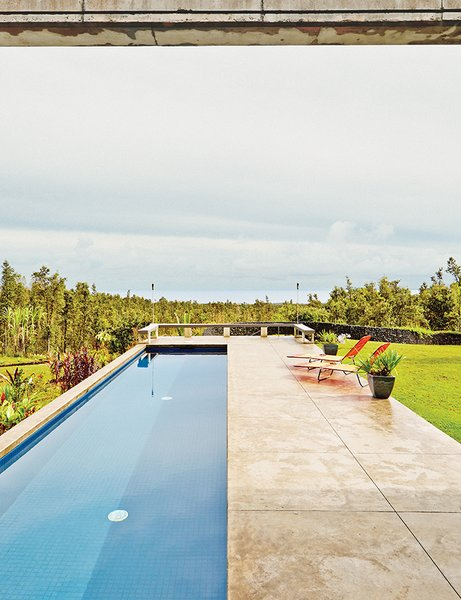 The pool juts out perpendicularly from the main house; the land was bulldozed to become level with the concrete pavers.
