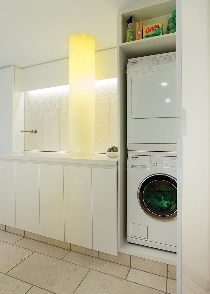 The focal point of the sleek, white space is a glowing laundry chute illuminated from within by fiber-optic cables.  Photo 2 of 5 in Bright Modern Laundry Room We'd Actually Like to Spend Time In