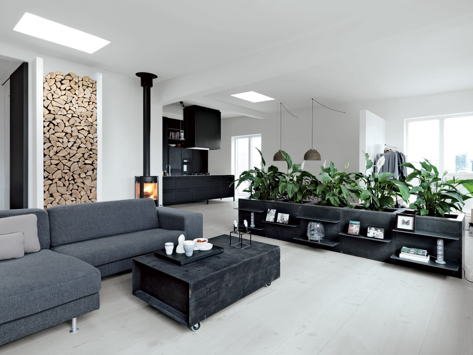 """The living room features a sofa from Engell; a suspended Parentesi lamp by Achille Castiglioni and Pio Manzù for Flos (Olsen's """"all-time favorite""""); and a wood-burning stove made by Aduro. The firewood nook set in the left wall is Jensen's own design. Olsen is responsible for the low planters around the perimeter, which she had fabricated from poured concrete framed in welded iron, with lacquered MDF panels for doors. """"Some people laughed because we'd never had plants in our apartment,"""" she says. """"So when we wanted a hedge, our friends were, like, Ok. Really? Good luck with that."""""""