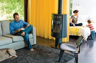 10 Cozy Wood-Burning Stoves For Riding Out the Last Bit of Cold Weather - Photo 7 of 10 - A Rais Pina wood-burning stove keeps things cozy on the West Elm Henry sofa and Eames lounge chairs.