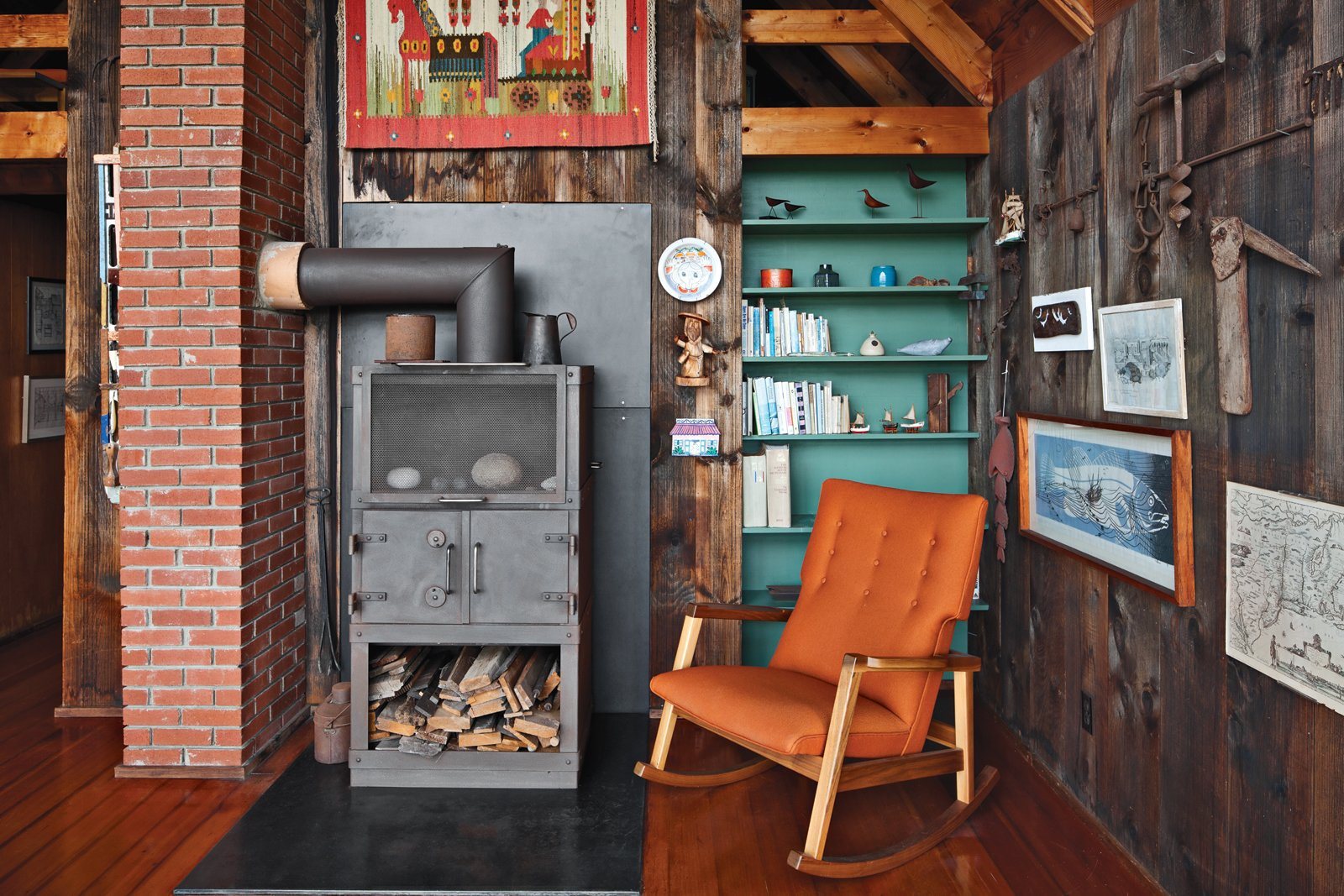 Inside the house, a relatively new Rais wood-burning stove is next to a Risom Rocker from Design Within Reach, a 2009 piece from the designer. Tagged: Living Room, Medium Hardwood Floor, Chair, Wood Burning Fireplace, and Shelves.  Photo 3 of 13 in Jens Risom's Block Island Family Retreat