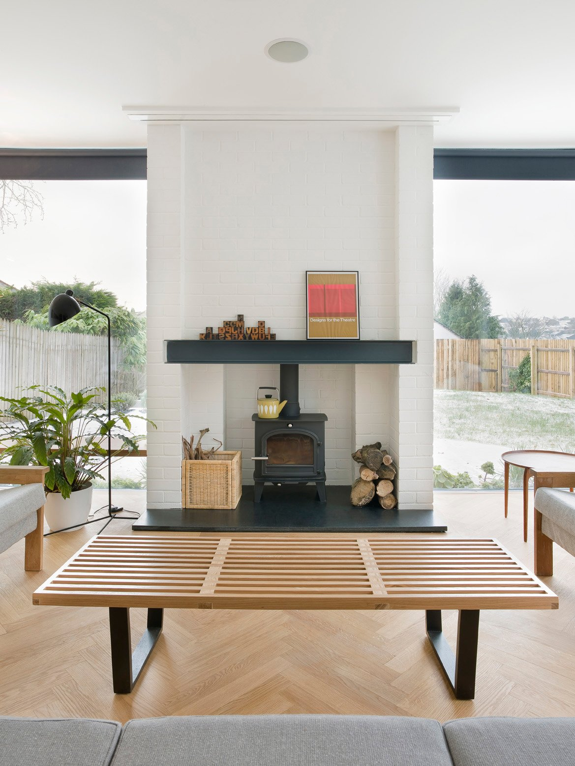 In the living room, a Nelson bench doubles as a coffee table, and a wood-burning stove from Cleanburn Stoves keeps the space warm. Tagged: Living Room, Ceiling Lighting, Light Hardwood Floor, Bench, and Wood Burning Fireplace.  Modern Wood-Burning Stoves by Megan Hamaker from An Obsessed Designer Fills Her Home with Vintage Finds