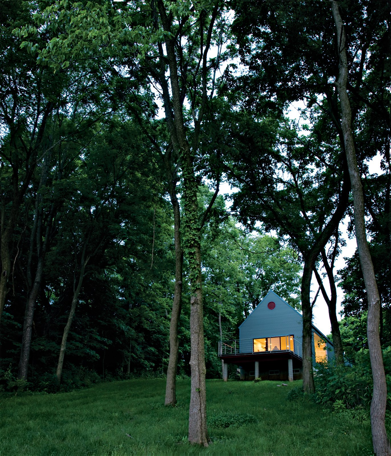 Lauren Ewing's stylish but unassuming shotgun-style house in Vincennes, Indiana, is set into a hill overlooking a field she has known since childhood. Tagged: Grass, Trees, Slope, Back Yard, Exterior, and House.  Photo 1 of 10 in Bringing It All Back Home