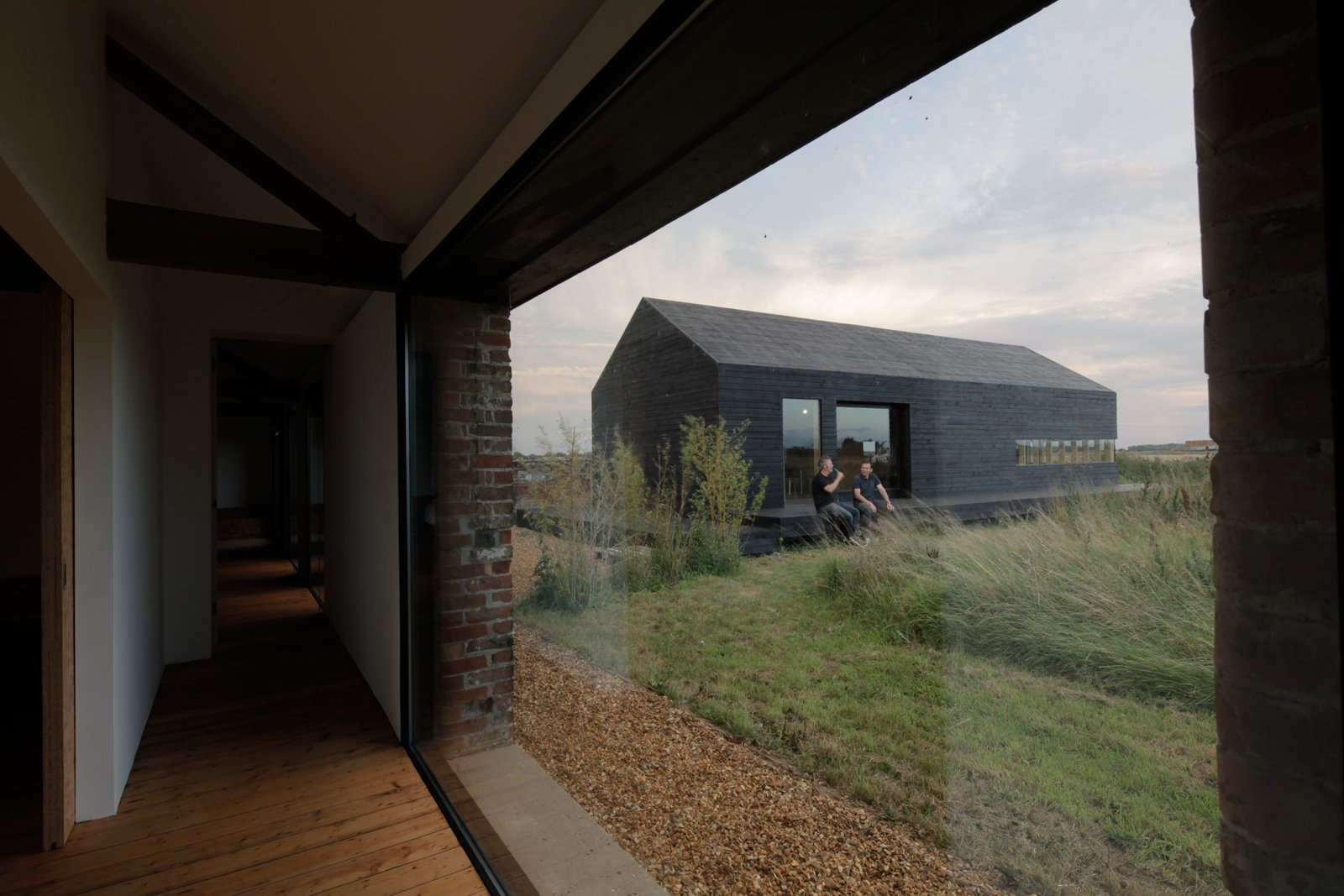 The two structures are in constant dialogue. Not only are their forms in sympathy, but as they're set at right angles to one another, they are rarely out of view.  Photo 10 of 12 in A Pair of English Barns Hide Unabashedly Bold and Budget-Friendly Minimalist Interiors