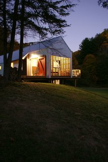 Farmhouse Redux - Photo 13 of 13 - The new home's porches glow like lanterns at night. Image courtesy Chad Everhart Architect.