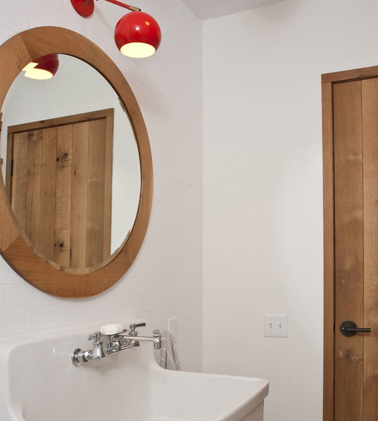 Nico shares the downstairs bathroom with any overnight guests who may be visiting. The circular mirror, framed in white oak, was designed and made by Materia Designs, based in Kerhonkson.  Photo 6 of 10 in An Enclave of Modern Cottages in New York's Hudson Valley