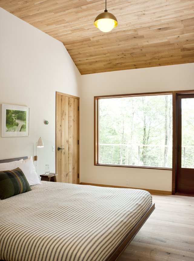 White oak makes a return appearance on the ceiling in the master bedroom. Tagged: Bedroom, Bed, and Medium Hardwood Floor.  Photo 7 of 10 in An Enclave of Modern Cottages in New York's Hudson Valley