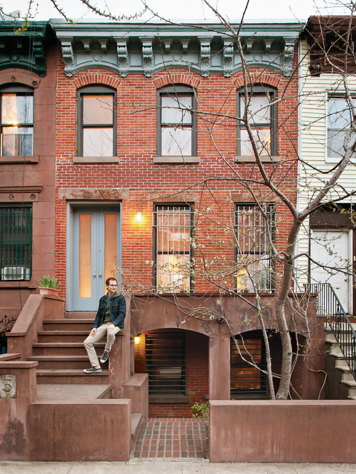 Sherman sits in front of his Prospect Heights home. The front door is made from etched Lexan bulletproof glass.  New York City Row House Renovations We Love by Zachary Edelson from New Prospects