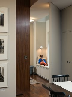 Houldin, 10, curls up in the playroom nook which is directly under a side skylight that Pulltab added in order to make the interior rooms inhabitable, as per New York City building code. The custom millwork around the window seat is painted in Rainy Day by Fine Paints of Europe.