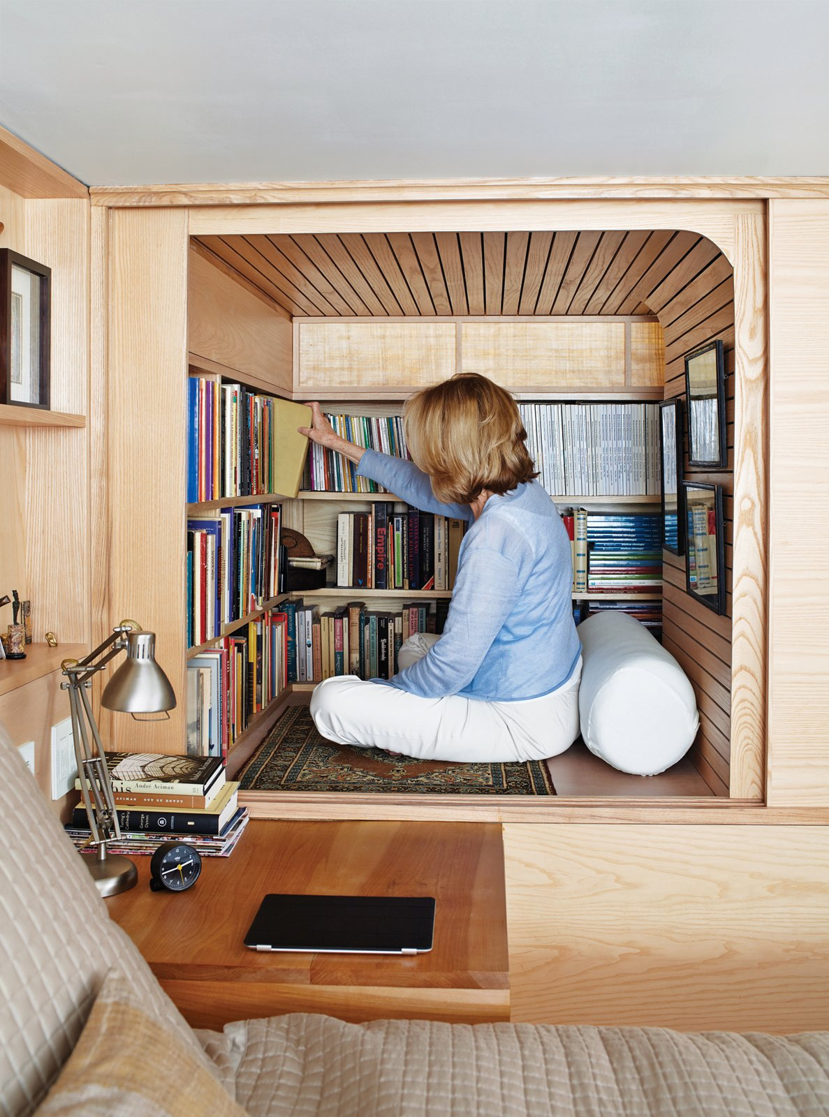 "Visiting a Manahttan apartment designed by Tim Seggerman is like sitting inside one of Nakashima's cabinets, a metaphor realized most fully in an ingenious ""library""—really just a glorified cubby with a banded maple ceiling, conjured from a free space adjacent to the loft bed. Tagged: Bedroom, Bookcase, and Storage.  Photo 1 of 8 in Space-Saving Wood-Paneled Apartment in Manhattan"