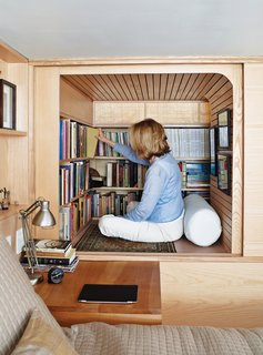 "Cozy and Compact: 10 Tiny Homes in the Big Apple - Photo 3 of 10 - Visiting a Manahttan apartment designed by Tim Seggerman is like sitting inside one of Nakashima's cabinets, a metaphor realized most fully in an ingenious ""library""—really just a glorified cubby with a banded maple ceiling, conjured from a free space adjacent to the loft bed."