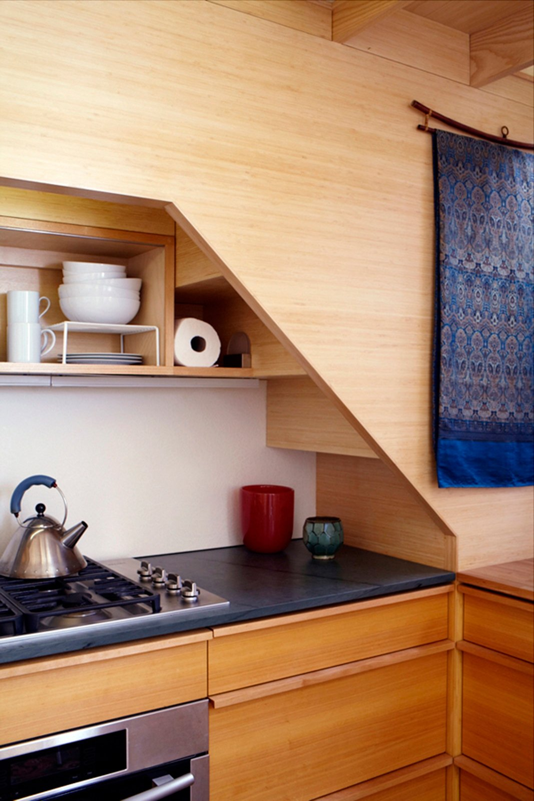 Inspired by mid-century furniture designer George Nakashima, Seggerman crafted the components by hand in his home studio. The cabinetry in the kitchen and shelving in the bedroom seamlessly flow, adding the impression that there is more space. Photo by David Engelhardt. Tagged: Kitchen and Concrete Counter.  Photo 7 of 8 in Space-Saving Wood-Paneled Apartment in Manhattan