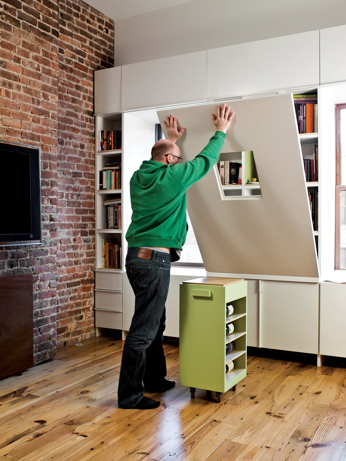 The table's base, which itself is an additional storage container, rolls easily into place to support the surface.  Tiny Apartments in New York City by Allie Weiss from Storage-Smart Renovation in New York City