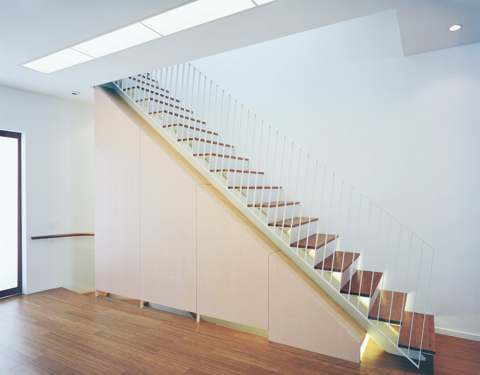 Briggs and Knowles's elegant staircase draws upon the language of the oculus; the stairs are underlit with fluorescent lighting, which accents the line of the steps, giving them an ethereal, almost weightless quality. Tagged: Staircase, Metal Railing, and Wood Tread.  190+ Best Modern Staircase Ideas by Dwell from Modern Rowhouse Renovation in New York