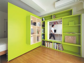 Shibata wanted more shelf space in her home office, so she added a plywood door with built-in bookshelves that opens into her bedroom to form a reading nook. Glimpsed from the adjacent room, the space looks larger than it actually is, thanks to the bright green walls.